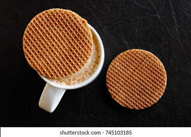 White mug with milky frothy coffee and a round waffle biscuit on top next to another waffle biscuit isolated on black leather from above.