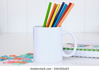White mug mockup. Blank mug. Coffee mug mockup with colored pencils , paperclips, notebooks. 11 oz