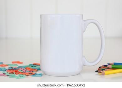 White mug mockup. Blank mug. Coffee mug mock up with colored pencils , paperclips. 15 oz