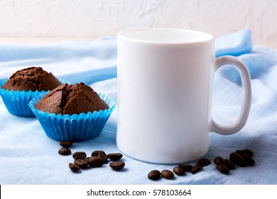White mug mockup with coffee beans and two chocolate muffins.  Empty mug mock up for design presentation.