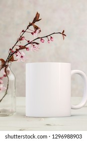 White Mug Mockup - Easter or Spring theme. Blank white mug next to blossom  in a glass vase. Perfect for businesses selling mugs, just overlay your quote or design on to the image.