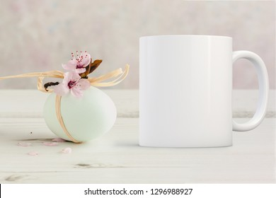 White Mug Mockup - Easter or Spring theme. Blank white mug next to a little sprig of blossom, on a table top. Perfect for businesses selling mugs, just overlay your quote or design on to the image.