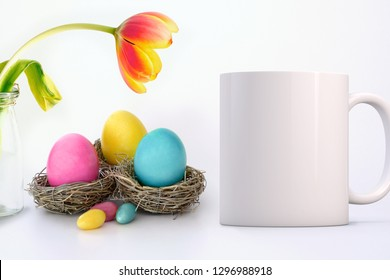 White Mug Mockup - Easter theme. White blank mug next to coloured eggs in nests and a pretty vibrant tulip. Perfect for businesses selling mugs, just overlay your quote or design on to the image.