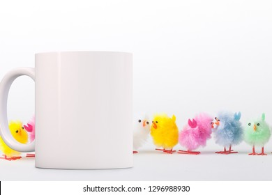 White Mug Mockup - Easter theme. Cute fluffy toy chicks behind a white blank mug. Perfect for businesses selling mugs, just overlay your quote or design on to the image.