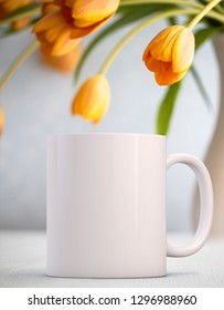 White Mug Mockup - Easter theme. Blank white mug next to pretty orange tulips. Perfect for businesses selling mugs, just overlay your quote or design on to the image.
