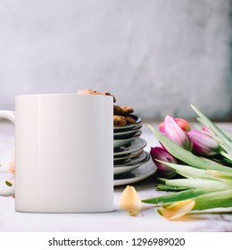 White Mug Mockup - Easter theme. Blank mug infront of a plate of cookies with a bunch of tulips on a table top. Perfect for businesses selling mugs, just overlay your quote or design on to the image.