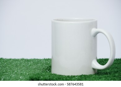 A white mug on the artificial grass with white background.