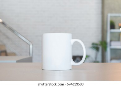 White mug on table and modern room background. Blank drink cup for your design. Can put text, image, and logo.
