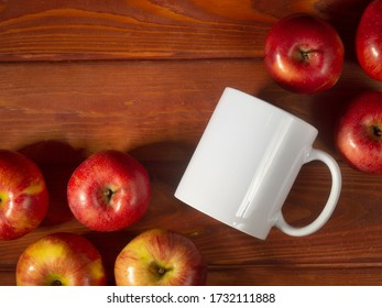 white mug on a wooden brown background with red ripe apples, a mug for sublimation, space for your text, flat lay