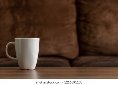 White mug on a wooden table with a brown couch background. copy space left over for text and images