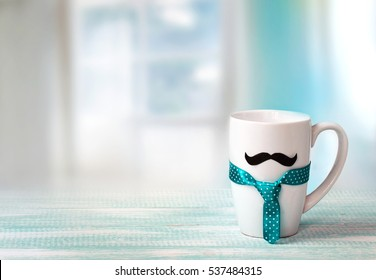 White mug on wooden table with mustache and tie indoors blue empty space background.Fathers day concept.Masculine wallpaper.