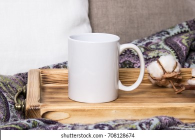 White mug on a wooden tray, the Mockup. Cozy home, linen and wool decorations.