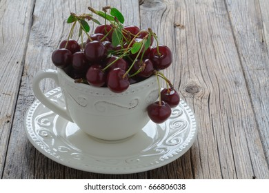 White mug with ripe cherries on old wood background