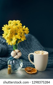White mug of strong coffee with marmalade next to yellow chrysanthemum flowers in a glass transparent vase and tied cotton