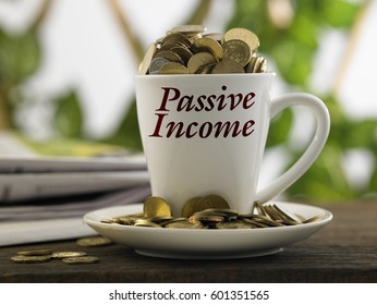 white mug written passive income with coins inside, finance conceptual.