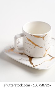 White mugs with a saucer. Cups for coffee and tea on a white background. Utensils for any holiday, luxury wedding, birthday or party. Style Japanese art of repair broken dishes, kintsugi. Gold streaks