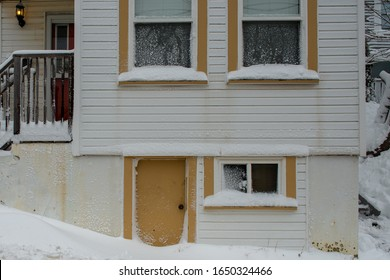A white multi storey building with beige trim. There's windows, doors and steps with a rail on the house. There's snow on the window ledges and piled in front of the door after a recent snow storm.
