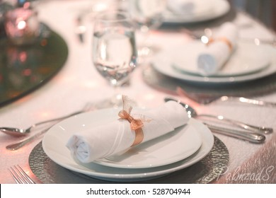 White napkin with golden ribbon on white dish , glasses and spoon