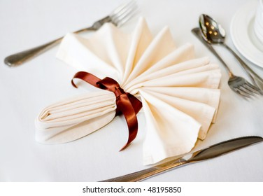 white napkin and place setting with brown ribbon and flatware on a white tablecloth