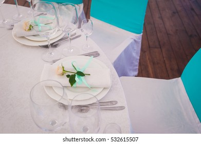 The white napkin which is tied up by a tape and with a small rose lies on a lunch plate. Festive table layout for a lunch.