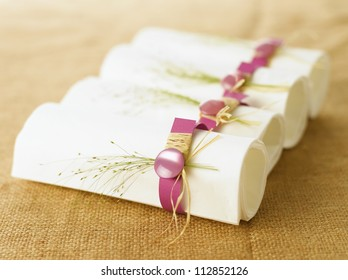 White napkins in pink napkin ring sitting on a plate. Linen textile background. Shallow DOF.