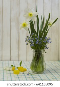 White narcissus and forget-me-not in a glass vase. Spring flowers and yellow bonbon candies on table, with wood background.