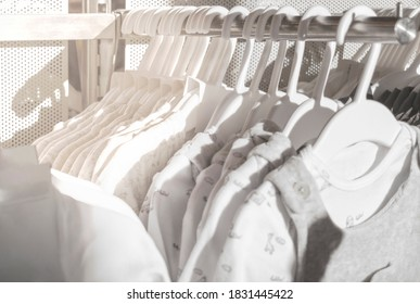 White natural clothes for children hanging on rack in the store. Baby clothes made from organic fabrics. Abstract background. Selective focus