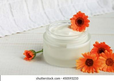 white natural cosmetic cream for face and body skin care,anti-acne treatment, holistic calendula blossom fresh flowers, white towel.