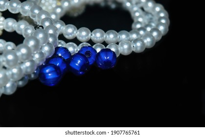 White necklace with blueish beads on a black surface