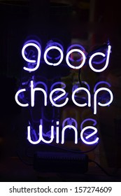 A white neon sign reading Good Cheap Wine