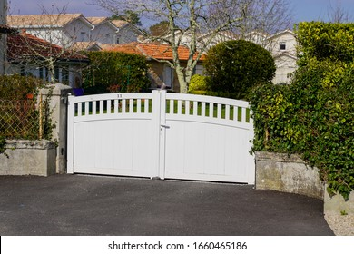 white new metal driveway entrance home gates in modern suburb house