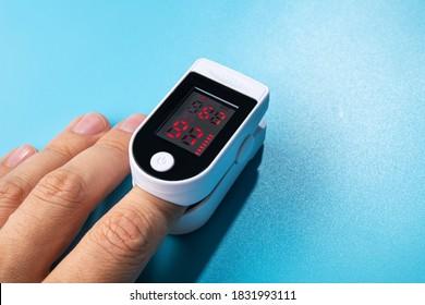 Weißes neues Pulsoximeter auf einem blauen Tisch. Messung des Blutdrucks und des Sauerstoffgehalts. Pandemieuntersuchung, Covid 19. die Hand des Patienten.