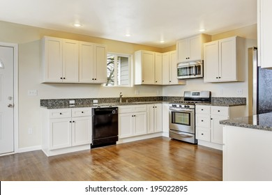 White new small simple classic American kitchen interior. Shiny hardwood floors.