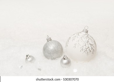 white new year background with christmas balls on an artificial snow