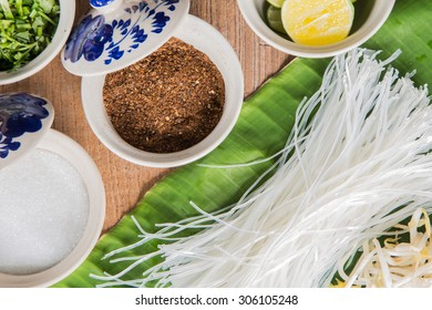 White noodles and seasoning on the wood background