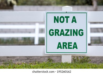 White not a grazing area sign mounted on a wooden fence with green letters outside of an equestrian arena.