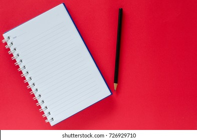 White note book and black pencil on brown color background with copy space.
