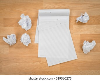 White note book paper with crumpled paper on a wooden desk
