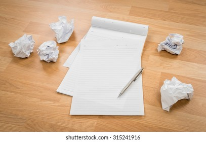 White note book paper with pencil and crumpled paper on a wooden desk