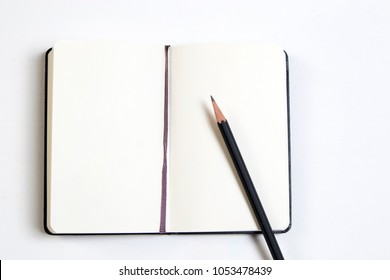 white notebook and a black pencil on a white wooden table.