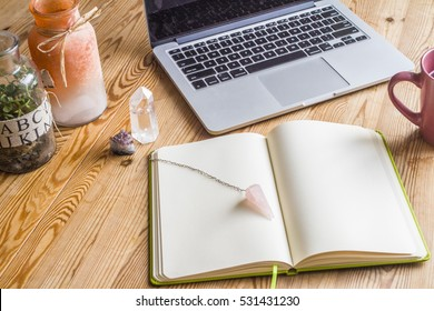 White notebook on wooden table with crystals, laptop and coffee