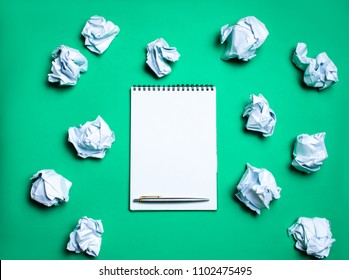 white notebook with pen on a green background among paper balls. The concept of generating ideas, inventing new ideas. Paper balls are all around. Searching of decisions. Bad idea. Business