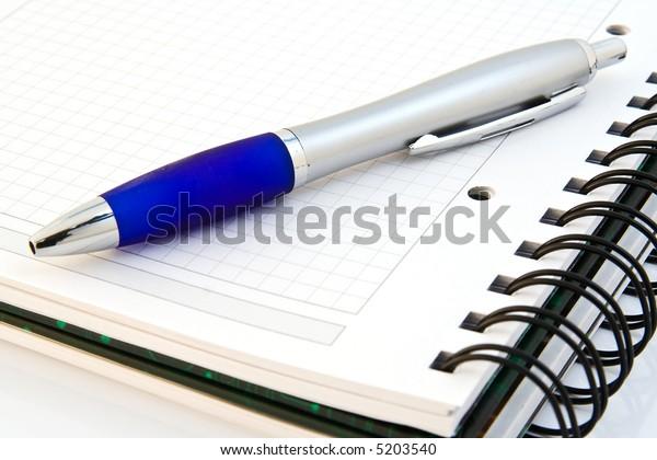 White notebook witk silver ballpen over white background