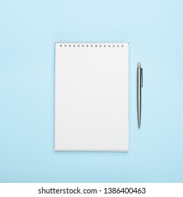 White notepad with metal pen on a blue background. Office, copy space, mock up, template, top view, flat lay.
