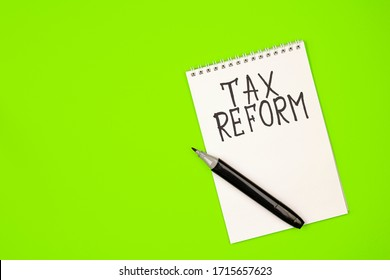 a white Notepad with the words tax reform and a black marker on a green background. the concept of the need for tax reform in the country