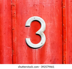 White number 3 sign on a red wooden door panel with two metal strips on either side in a close up full frame view