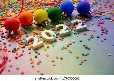 Chiffres blancs 2022 avec des saupoudrées de sucre couleur sur une table en pierre avec des balles de couleur