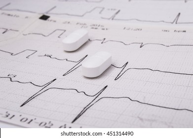 White oblong pills or tablets (for treatment of diseases of the cardiovascular system as an option - statin) lie on the paper electrocardiogram (EKG or ECG)