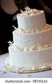 a white ocean themed wedding cake with miniature seashell design and details