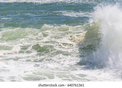White ocean waves crashing over coastal sea rocks in summer
